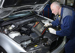 Mechanic repairing a car at Norman hand Services, Neston.
