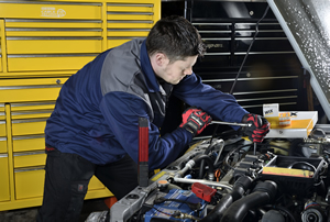 Mechanic carrying out repairs under the bonnet of a car.